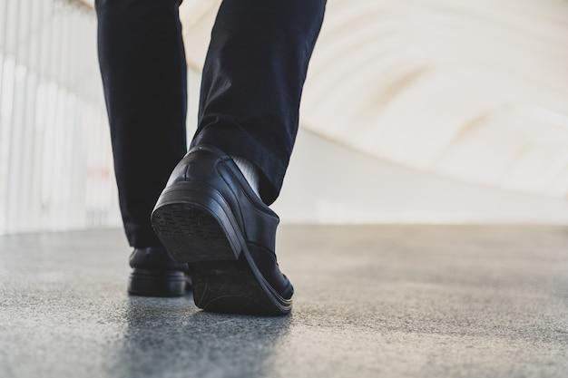 Gambe di uomo d'affari a piedi