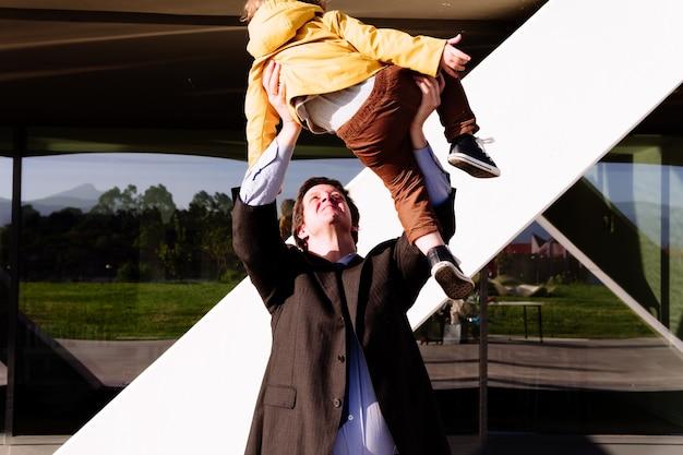 Uomo d'affari che solleva in aria suo figlio di 3 anni. concetto di amore dei genitori. giocare con i bambini. famiglia