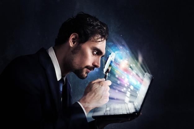 Sguardo dell'uomo d'affari con la lente d'ingrandimento sullo schermo del computer