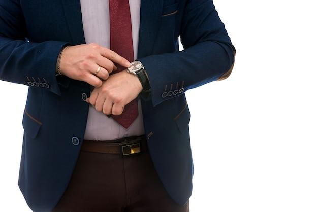 Uomo d'affari che guarda l'orologio prima della riunione d'affari isolato