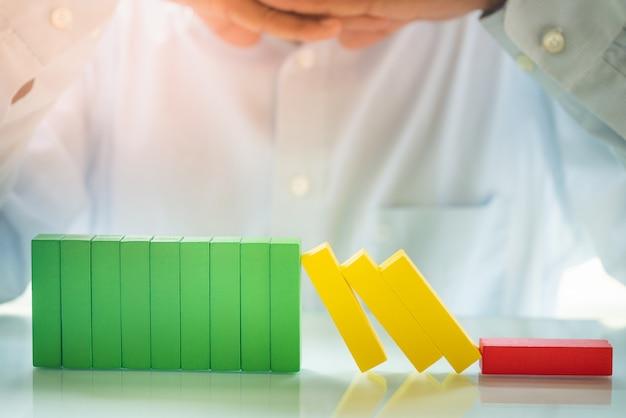 Uomo d'affari che esamina effetto di domino del blocchetto di legno del giocattolo. l'unità è concetto di potere.