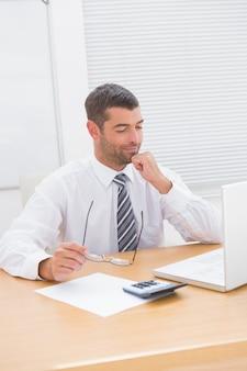 Uomo d'affari guardando il suo portatile alla sua scrivania