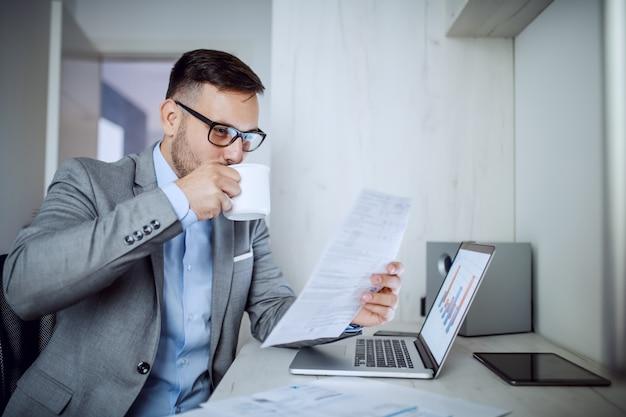 Uomo d'affari che esamina lavoro di ufficio e che beve caffè.