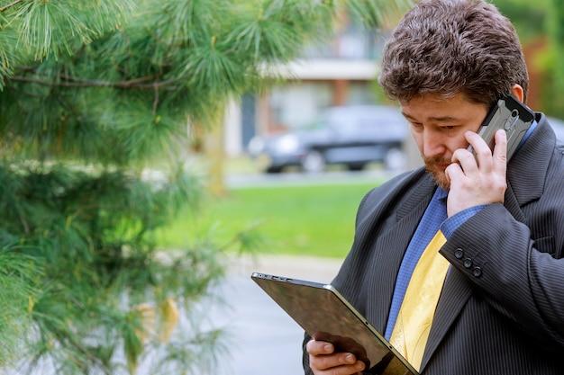 Uomo d'affari che esamina telefono nella rete sociale che manda un sms sul telefono.