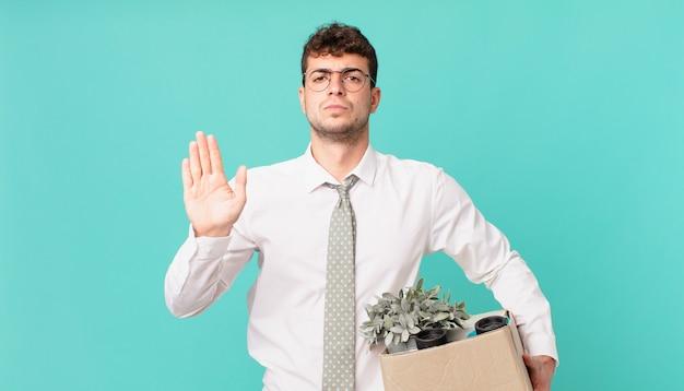Uomo d'affari che sembra serio, severo, dispiaciuto e arrabbiato che mostra il palmo aperto che fa il gesto di arresto. concetto di licenziamento