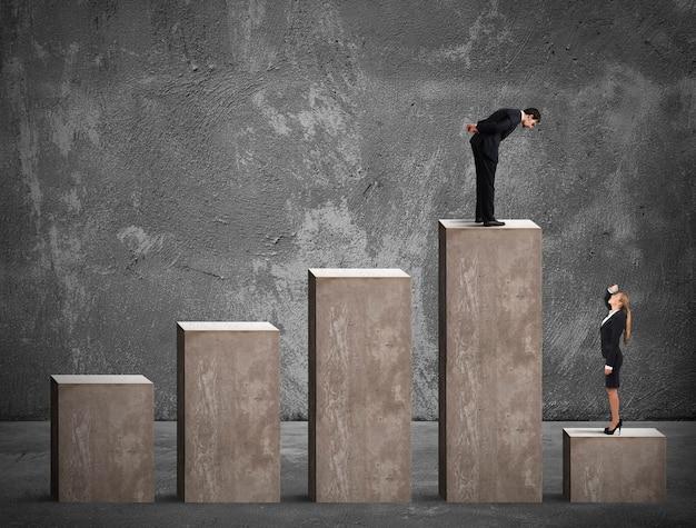 L'uomo d'affari guarda una donna d'affari nel gradino più basso della statistica