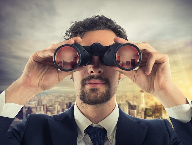 L'uomo d'affari guarda la città dal tetto con il binocolo
