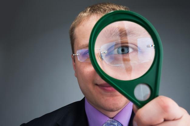 L'uomo d'affari ti guarda attraverso la lente d'ingrandimento