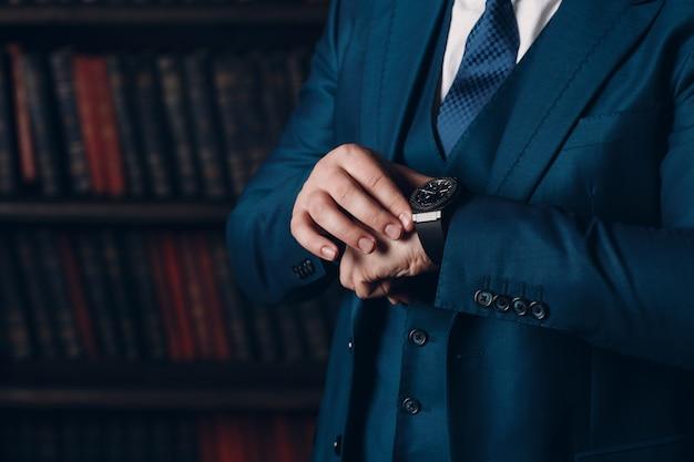 L'uomo d'affari in un vestito di lusso esamina l'orologio