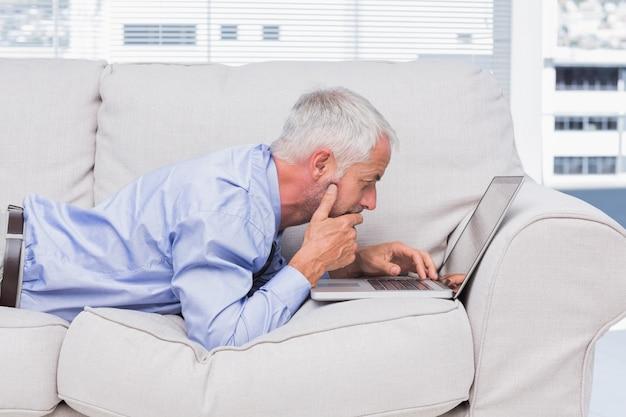 Uomo d'affari che si trova sul divano con il portatile