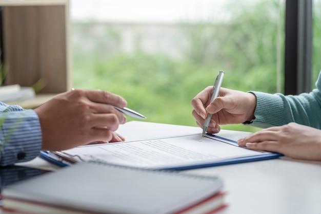 Uomo d'affari che fa un accordo di collaborazione con in mano una penna per firmare un contratto in ufficio