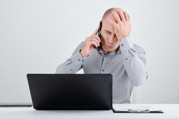 Uomo d'affari che fa il gesto del palmo del viso quando parla al telefono con il manager del progetto fallito