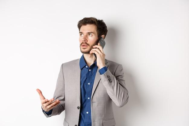 Uomo d'affari che fa telefonata, parlando su smartphone e guardando occupato, indossa una tuta, sfondo bianco.