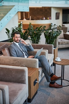 Uomo d'affari che fa una telefonata in una sala d'attesa