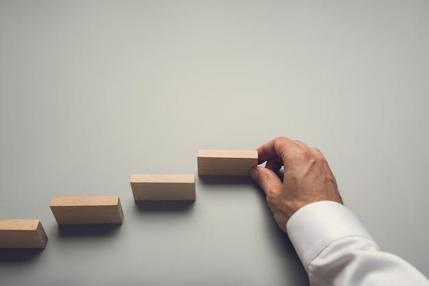 Imprenditore facendo passi verso il successo inserendo pioli di legno su uno spazio grigio.