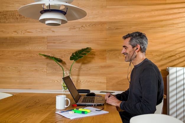 Uomo d'affari che fa una videoconferenza nel suo salotto con un laptop e auricolare