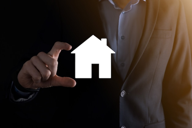 Icona della casa della tenuta della mano maschio dell'uomo d'affari su priorità bassa blu. assicurazione di proprietà e concetto di sicurezza. concetto di bene immobile. banner con spazio di copia.