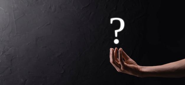 I punti interrogativi dell'interfaccia della tenuta della mano dell'uomo dell'uomo d'affari firmano il web. fai domande online, concetto di faq, cosa dove quando come e perché, cerca informazioni su internet