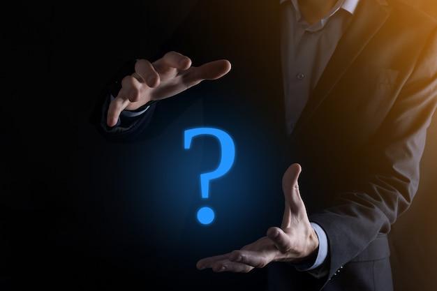 Uomo d'affari man mano tenere interfaccia punti interrogativi segno web. chiedi informazioni in linea, concetto di faq, cosa dove quando come e perché, cerca informazioni su internet.