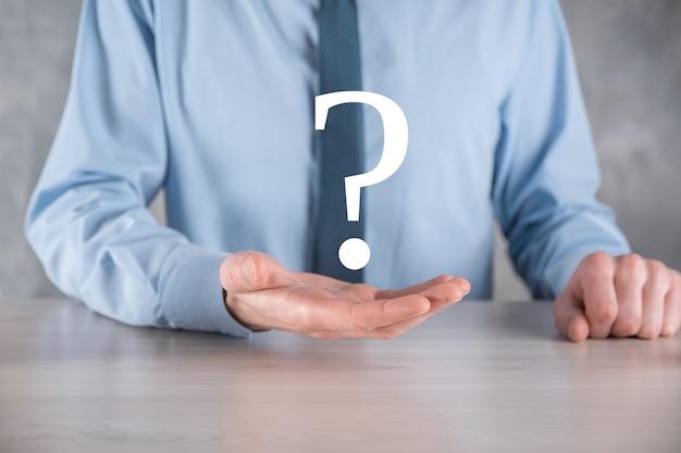 Uomo d'affari man mano tenere interfaccia punti interrogativi segno web. chiedi informazioni online, concetto di faq, cosa dove quando come e perché, cerca informazioni su internet.