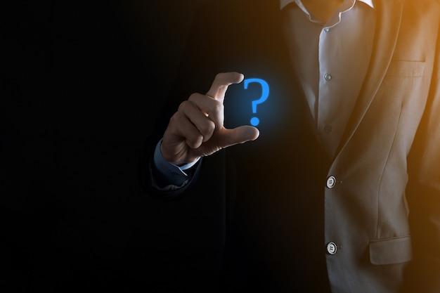 Uomo d'affari man mano tenere smartphone interfaccia telefono punti interrogativi segno web. chiedi informazioni online, concetto di faq, cosa dove quando come e perché, cerca informazioni su internet