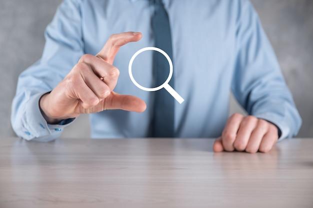 Uomo d'affari, uomo tenere in mano icona lente di ingrandimento. affari, tecnologia e concetto di internet