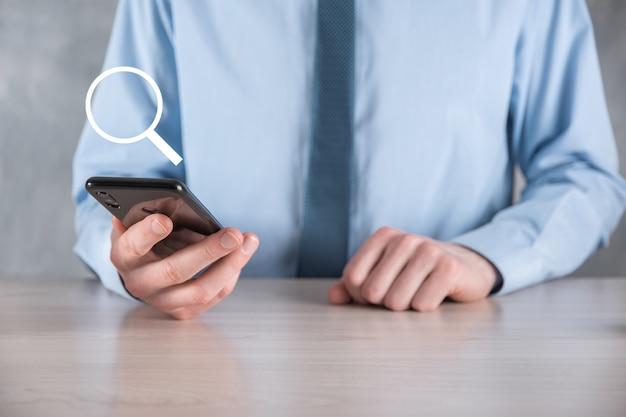 Uomo d'affari, uomo tenere in mano la lente d'ingrandimento icon.business, tecnologia e internet conceptbusiness