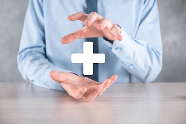 Uomo d'affari, uomo tenere in mano offrire cose positive come profitto, benefici, sviluppo, csr rappresentato dal segno più. la mano mostra il segno più.