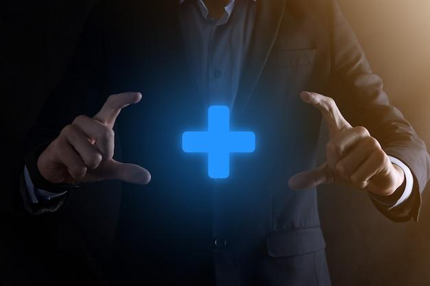 Uomo d'affari uomo tenere in mano offrire qualcosa di positivo come lo sviluppo dei benefici di profitto csr rappresentato dal segno più la mano mostra il segno più