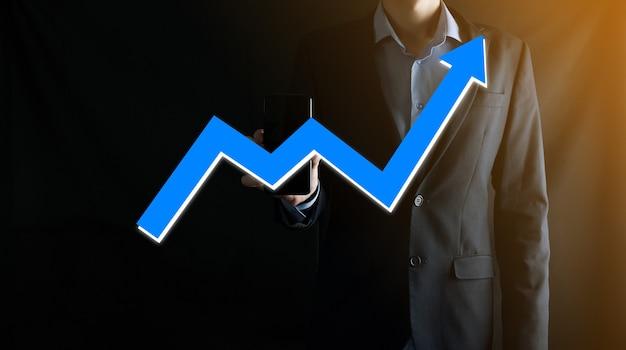 Uomo d'affari che tiene un grafico con una crescita positiva dei profitti. pianificare la crescita del grafico e l'aumento degli indicatori positivi del grafico nella sua attività. più redditizia e in crescita.