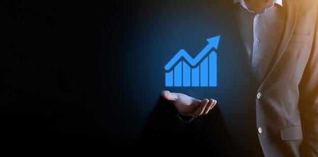Uomo d'affari che tiene un grafico con una crescita positiva dei profitti. pianificare la crescita del grafico e aumentare gli indicatori positivi del grafico nel suo business.più redditizio e in crescita.