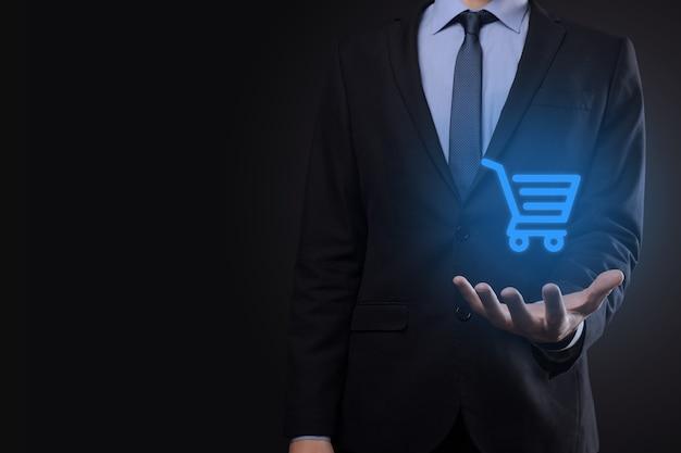 Uomo d'affari che tiene carrello carrello mini carrello nell'interfaccia di pagamento digitale aziendale.affari, commercio e concetto di shopping.