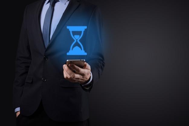 Uomo d'affari uomo tiene in mano clessidre icona. il tempo scade. un promemoria per l'azione.
