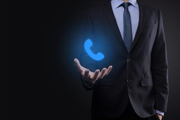 Uomo d'affari uomo in tuta su sfondo nero tenere premuto l'icona del telefono