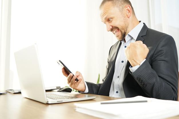 L'uomo d'affari esprime vividamente emozioni di gioia, sorpresa e felicità con un sorriso