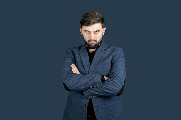 L'uomo d'affari, un uomo con la barba e un vestito blu, incrociò le mani davanti a sé