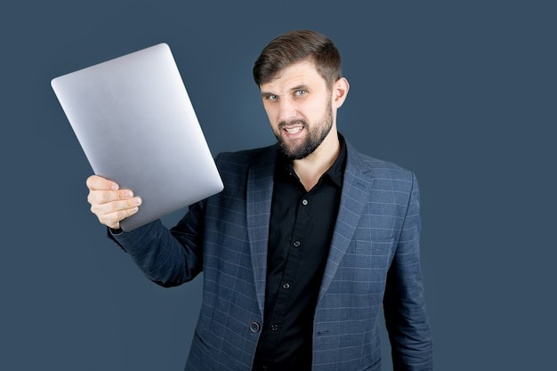 Uomo d'affari un uomo con la barba in un abito blu che tiene un laptop in una mano
