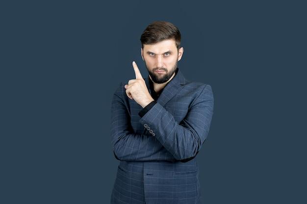 Un uomo d'affari, un uomo con la barba e un abito blu, mostra la direzione con il dito indice