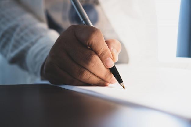 Il responsabile dell'uomo d'affari passa la penna di tenuta per il controllo e la firma dei documenti bianchi