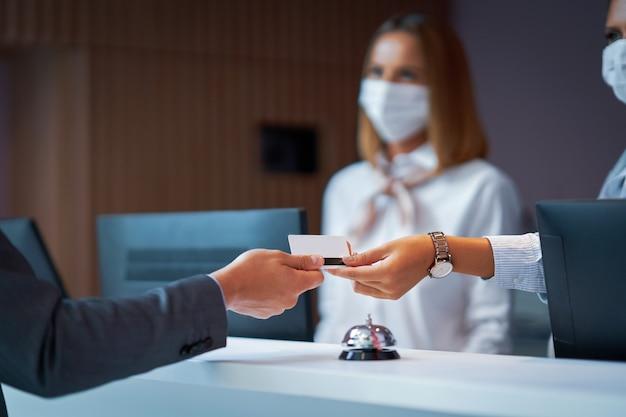 Uomo d'affari in maschera alla reception di un hotel che fa il check-in