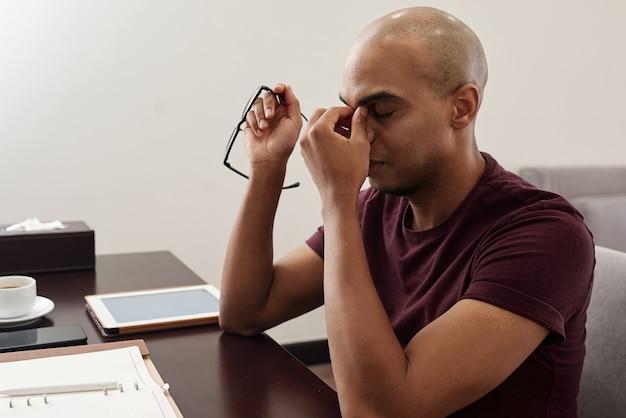 Uomo d'affari che massaggia il ponte del naso sensazione di affaticamento, da mal di testa o tensione agli occhi dopo aver lavorato troppo a lungo