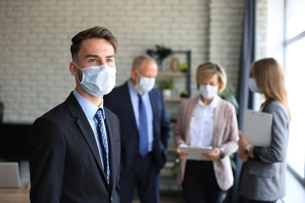 Uomo d'affari in maschera medica con i colleghi in background in ufficio.