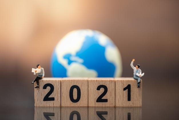 Figura in miniatura dell'uomo d'affari persone sedute, parlare e leggere il giornale sul blocco di legno numero 2021 con mini sfera del mondo.