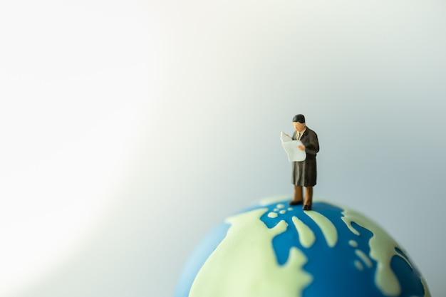 Imprenditore figura in miniatura persone in piedi e leggendo un giornale sulla mini sfera del mondo.