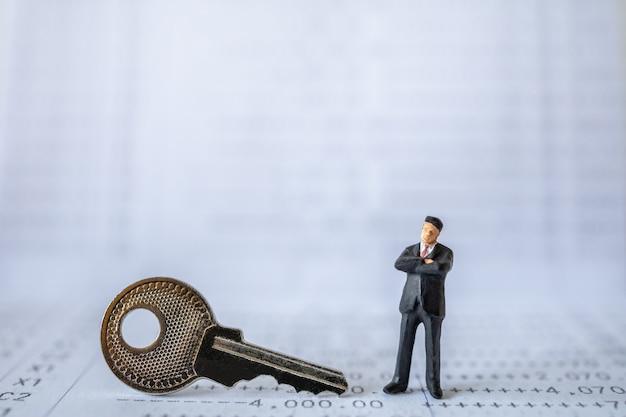 Uomo d'affari figura in miniatura persone in piedi con chiave d'argento sul libretto di banca