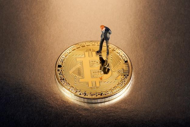 Figura miniatura dell'uomo d'affari che sta su un bitcoin