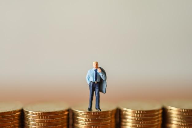 Imprenditore figure in miniatura persone in piedi in cima alla pila di monete d'oro con copia spazio