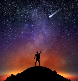 L'uomo d'affari su una montagna indica una stella cadente