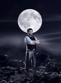 Uomo d'affari nella notte contro una grande luna