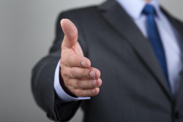 Uomo d'affari che offre la sua mano per la stretta di mano. saluto o gesto di congratulazioni. riunione d'affari e successo